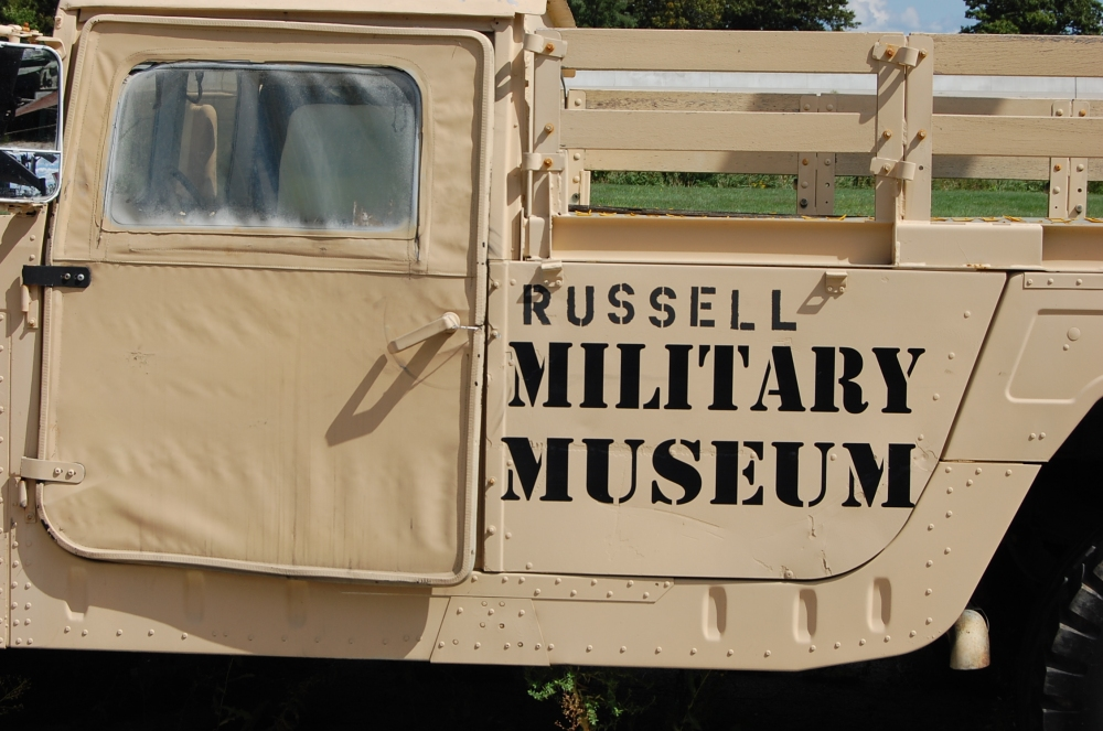 army truck painted desert tan with Russell Military Museum stencil in black on the side