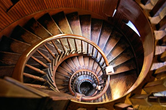 oval wooden spiral staircase that is well worn
