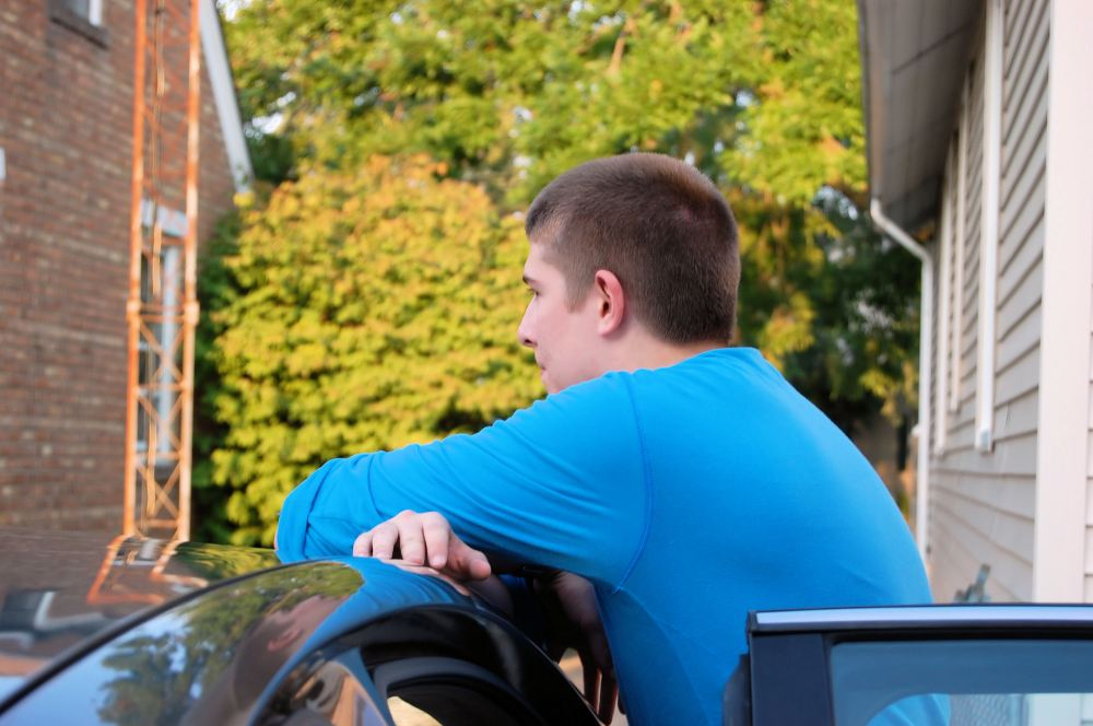 Aaron leaning on the roof of his car smiling and talking to his father