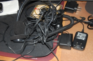 tangle of black cords to chargers, headphones, and such