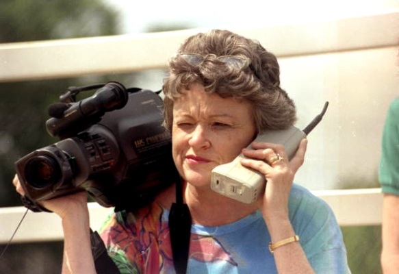 Journalist Lucy Morgan With Video Camera and Phone from  Florida Memory State Library and Archives of Florida as a member of The Commons on Flickr. No known copyright restrictions.