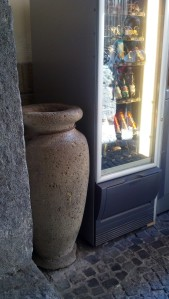 Ancient Roman wine urn next to modern vending.